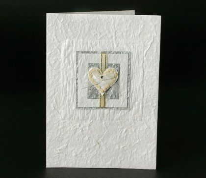 Handmade wedding invite. Made from handmade paper. It has a heart and ribbon on the front.www.kardella.com