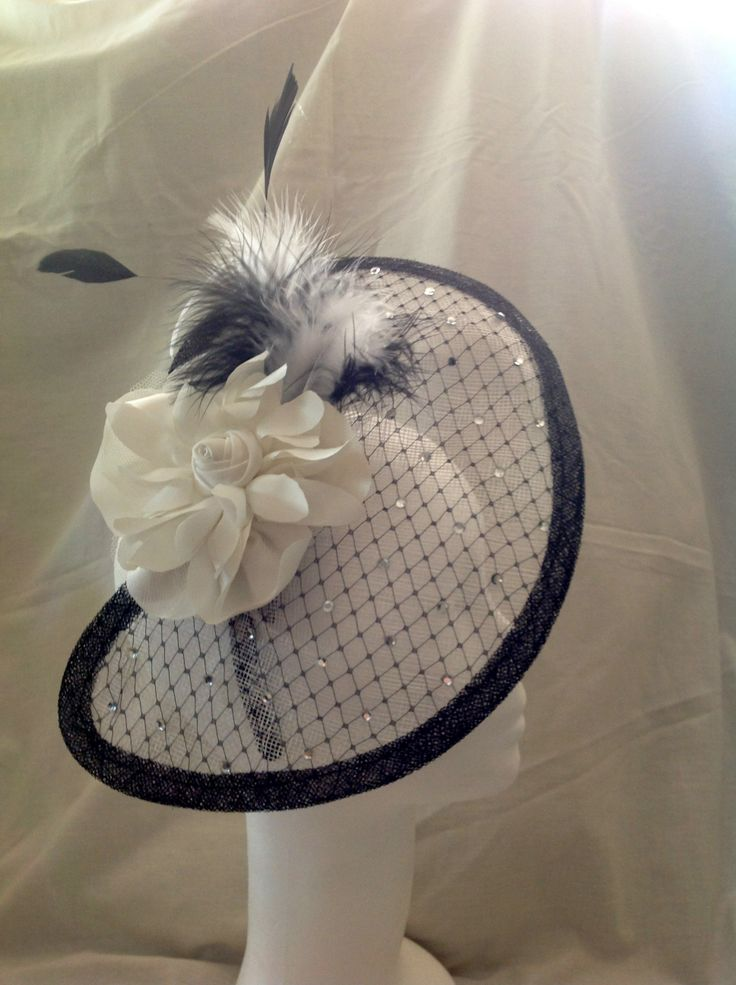 A fascinator by fascinators by Julie the Isabelle is a large fascinator on a black head band the base is large half moon shaped sinamay in diamond white with black trim the base is decorated with a diamante detailing throughout the centre piece is a large white flower surrounded by matching feathers. $140 AUD. Found in the Diamante collection on the website.