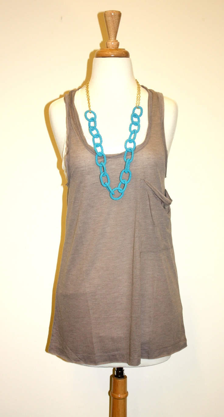 A light, brown tank top is paired with one of our new favorite summer necklaces.