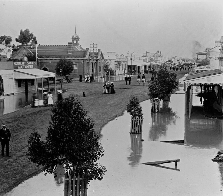 A flooded street in Warracknabeal. The Commercial Hotel is in the background on the right while the premises of Robert Smith, auctioneer is across the street. August 1909.