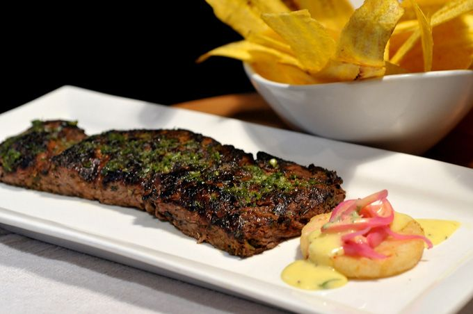 Churrasco (chargrilled center cut beef tenderloin, seasoned with chimichurri and served with crispy yuca cake, pickled onions & bearnaise sauce)