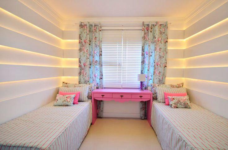 O destaque deste quarto projetado pela designer Marli Lima é a parede: painéis de MDF laqueados de brancas revestem a superfície e abrigam cordas luminosas, que produzem uma iluminação indireta e dão um clima romântico ao ambiente. O móvel em laca rosa foi desenhado pela profissional.