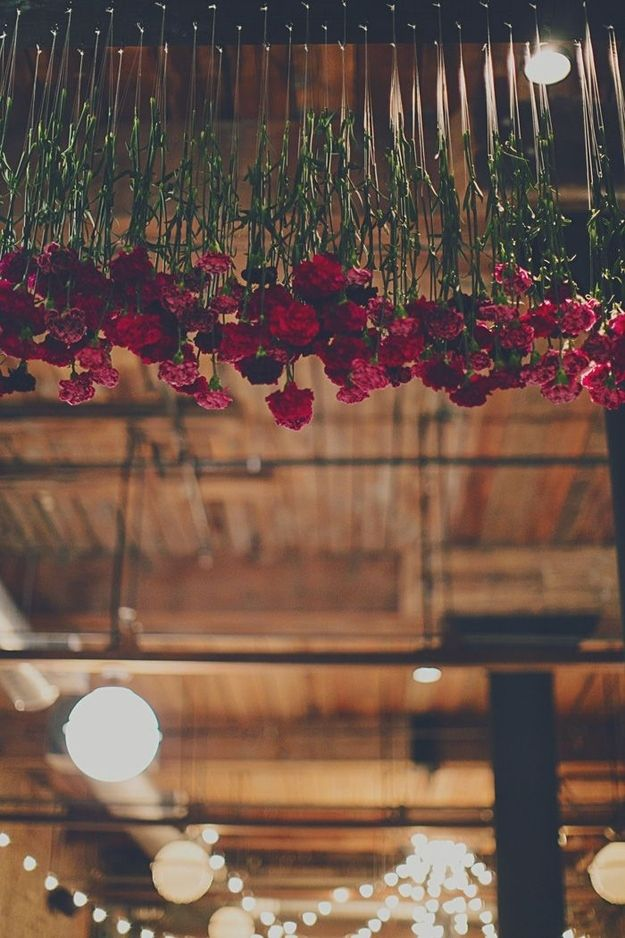 hang red roses or carnations from the ceiling. use fishing wire so they appear to be floating, or tie them with twine for a more rustic look. #weddings