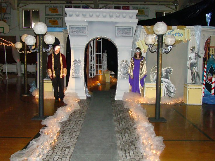 Italian themed prom, party decorations.   Light posts are carpet tubes with lanterns.   Backdrops are painted wood flats.   Statues are blown up and glued on cardboard.  Arch is from stumps prom.  Striped poles are cardboard tubes wrapped in red tape.