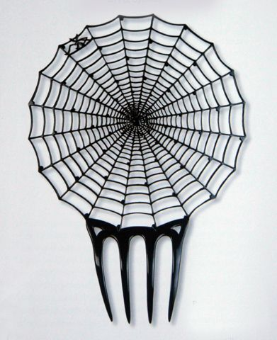 """Morticia Addams could not have dreamed of a more appropriate comb. This mantilla spiderweb was designed by Clément Joyard, c. 1910. He, along with Bonaz, Léon Arbez-Carme, and Marius Camet, were among the famous designers who had their combs made in the celluloid factories of France's Oyonnax Valley."""