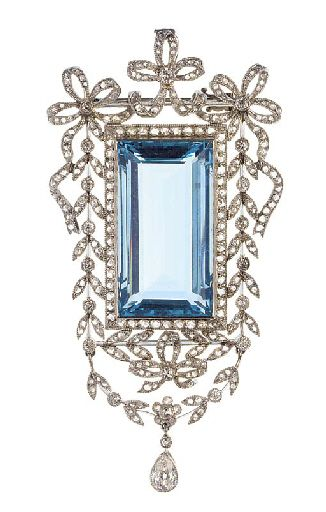 A Belle Epoque rectangular aquamarine and diamond brooch, the aquamarine in a rose-cut diamond frame with diamond and rose-cut diamond floral garland and bow surround, with garland terminal suspending a pear cut diamond drop, with hinged pendant loop.