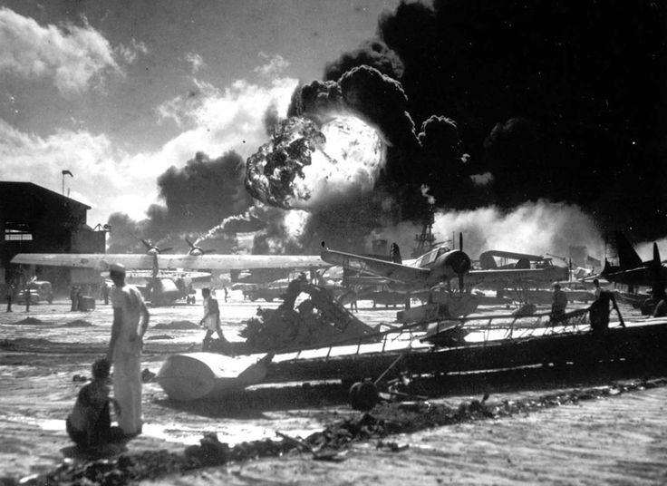 Sailors stand among wrecked airplanes at Ford Island Naval Air Station as they watch the explosion of the USS Shaw in the background, during the Japanese surprise attack on Pearl Harbor, Hawaii, December 7, 1941.