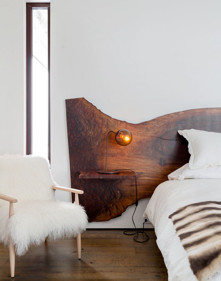 In the master bedroom is a custom-designed Claro walnut bed. A fuzzy Cortina chair from Refuge sits beside a Modo desk lamp by Jason Miller for Roll & Hill. (Photo: Trevor Tondro for The New York Times):