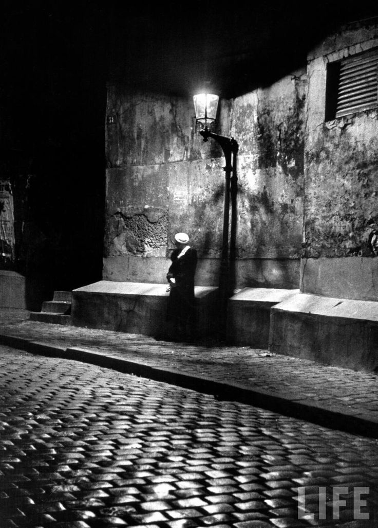 Alfred Eisenstaedt: Woman under streetlight in Montmartre at night. Paris, France, 1963