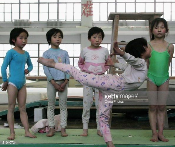 Young girls practise gymnastic movements at Chengdu Children's Gymnastics School on January 11, 2005 in Chengdu, China. There are around 3,000 sports schools in China, recruiting thousands of very young children and sending the elites to the country's Olympic machine. China has consistently risen in the Olympic medal table, coming second in Athens and will host the 2008 Olympic Games.