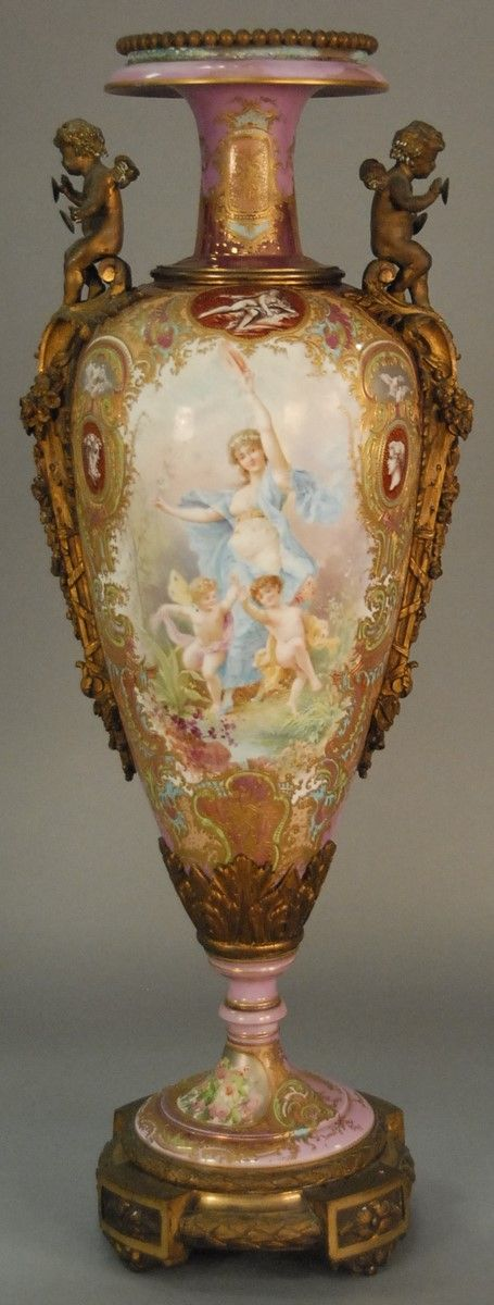 Sevres style gilt bronze mounted porcelain urn in baluster form having pink ground and painted cartouche depicting woman figure and cherubs on one side and landscape on the other, signed Collat, having heavy gilt decoration of scrolling leaves - Realized Price: $9,000.00