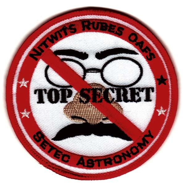 """The first letter of each word in the phrase """"Nitwits Rubes and Oafs"""" spells out the agency responsible for this patch: the NRO, the National Reconnaissance Office.Funny"""