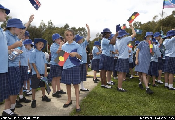 Primary school children wearing blue uniforms and holding Australian flags at the Apology to the Stolen Generations of Australia, Canberra, 13 February 2008 [picture]  Canberra : National Library of Australia, 2008.