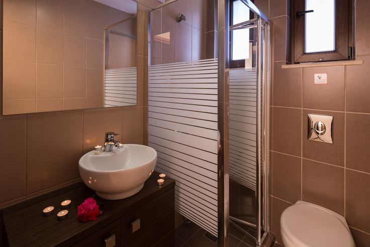 Bathroom interior design with shower, sink and toilet, complete with towels and hairdryer