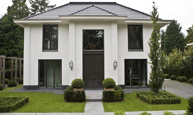 Eine große, weiße Villa mit dunklen eye catchern wie der Tür und den…
