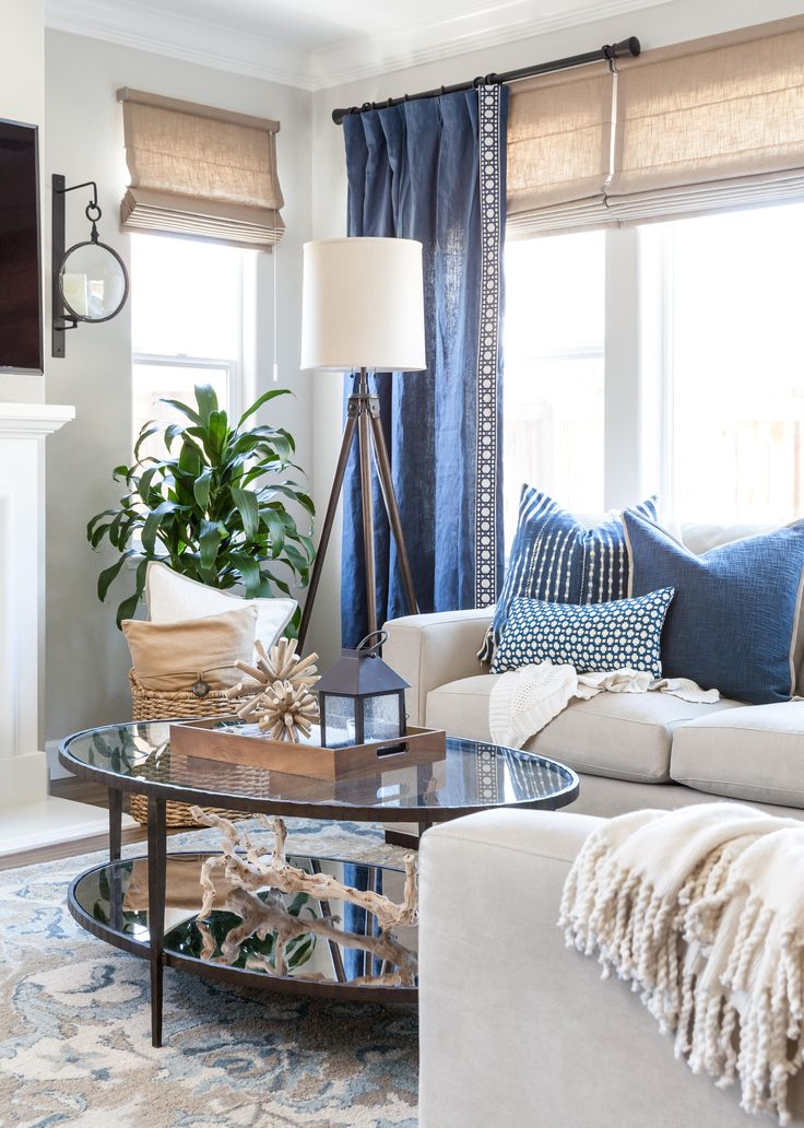 coastal family room blue and white pillows gray walls roman shades axis