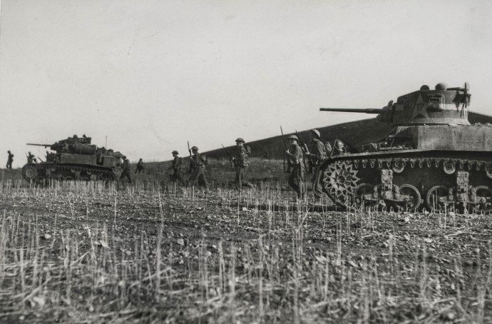 Two American M3 Stuart light tanks support a company of British infantry during the fighting in Tunisia in early 1943