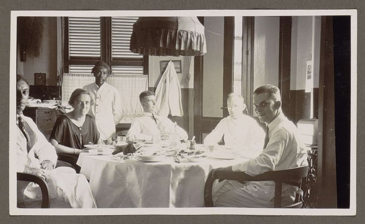 Anonymous | Indische bediende, mannen en een vrouw rondom een tafel, Anonymous, 1920 - 1930 | Vier mannen in witte kledij en een vrouw zitten aan een gedekte tafel met een wit tafelkleed. De raamluiken zijn gesloten. De stoffen kap van een hanglamp is nog juist zichtbaar. Staand voor het raam een Indische bediende met een hoofddeksel. Hij houdt zijn hand aan een schaal met serviesgoed.  Onderdeel van Familiealbum Nederlands-Indië.
