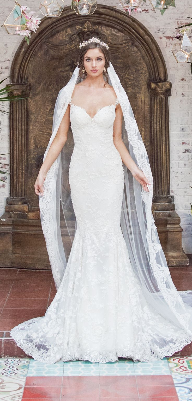 Desiree is our mermaid styled dress. It has a low open back and beaded lace details. The appliques are beaded with crystals. It has a sweetheart neckline with off-the-shoulder details and has a plunging open back. The gown comes with a detachable train which has an elaborate lace trim and cascading tulle details. #bride #wedding #couture