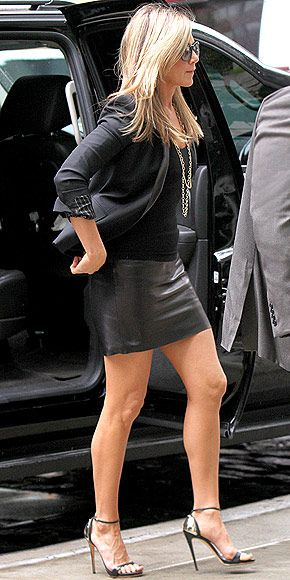 Jennifer Aniston in black leather mini skirt and black blazer with black Giuseppe Zanotti sandals.