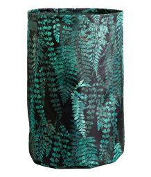 En skittentøyskurv i stødig polyester med trykt mønster, to hanker øverst og plastet innside. Diameter 34 cm, høyde 52 cm.