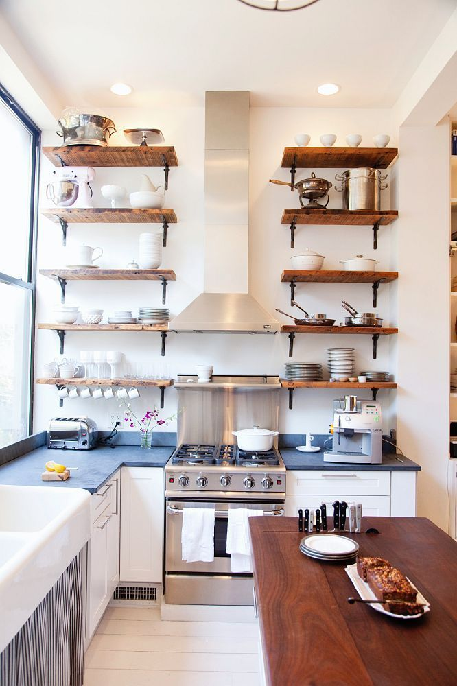 pequeña cocina en L con estanterías de madera hasta el techo