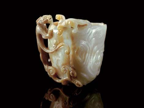 A Brown and White Jade Libation cup, Song-Ming Dynasty.   The cup well carved in the form of a tree trunk, the handle formed by a large CHI-dragon climbing up the sides with its head perched on the mouth rim facing a smaller dragon balancing on the rim, with a third CHI-dragon on the reverse writhing in and out of the surface, all supported on lingzhi fungus growing on the underside, the stone of semi-translucent white tones motfied with areas of opaque brown and some calcification.