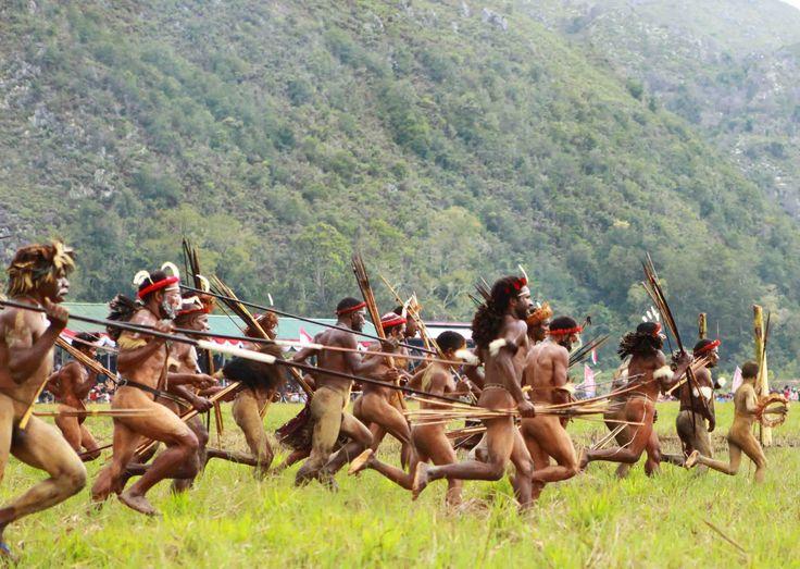 """Beberapa pemuda berlari, bersorak dan melakukan tarian tradisional di """"Festival Danau Sentani"""" Papua, Indonesia."""