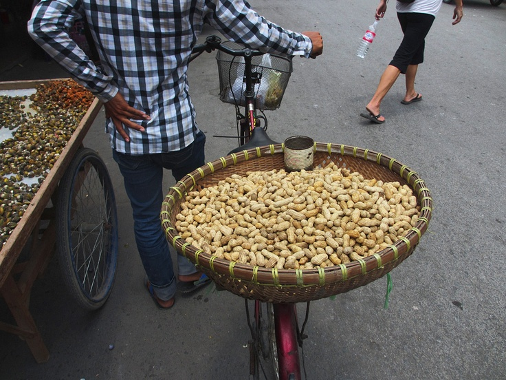 A peanut vendor stands beside his bicycle with hand on hip outside the Russian market in Phnom Penh. His body language maybe a sign of frustration from lack of sales (evident from the full basket)    Customers are opting for something which will quench their thirst, as daily temps hover around 37c.    It's not all doom and gloom for the peanut seller, as the peanuts are very popular during the evenings at the cities many bars and restaurants. They are absolutely delicious with a nice cold…