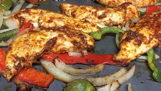 Make a sheet pan full of fajitas for a crowd with this easy and flavorful recipe combining chicken, peppers, onion, and a mix of seasonings.