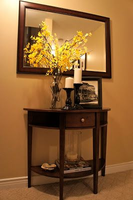 A mirror/ console table is a welcome addition at the bottom of the stairway. The mirror makes the space feel larger instead of feeling like a dead end. It also brightens the space by reflecting light.