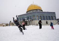 Children play in the snow in front of the Dome of the Rock in Jerusalem's Old City on February 20, 2015. More Global COOLING!!!!