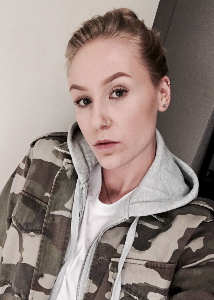 @onetakeanna nose piercing, camo jacket, hoodie, earrings, bun, blonde