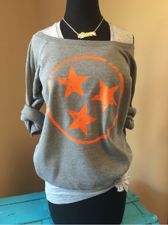 It's football time in Tennessee! Show your Vol Pride with this super comfy off the shoulder sweatshirt that features a distressed TN TriStar in traditional Volunteer Orange! Feminine, cozy and versati