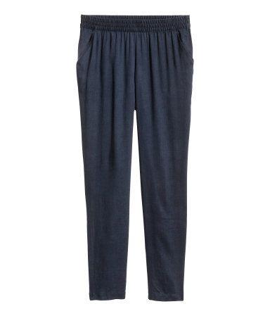 Mørkeblå. Vide bukser i let, vævet kvalitet. Bukserne har elastik i taljen, ben, der bliver smallere forneden, og sidelommer.