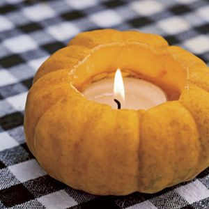 Pumpkin Votive | For an autumn table, carve out jack-be-little pumpkins and insert votive candles. This festive decoration is perfect for Thanksgiving feasts.
