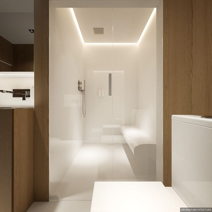 This small Scandinavian inspired shower uses unique lighting a long bench seat and white tile to create a feeling of size. The one level design also makes the space easy to enter