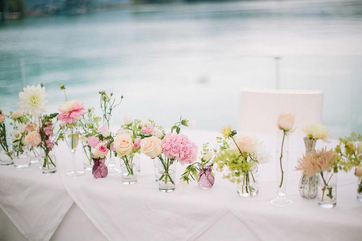 Unterschiedliche Väschen und Einmachgläser mit einzelnen Blüten in Creme, Gelb und Rosa bei der Trauung bei www.weddingstyle.de | Foto: Henry Welisch Photography