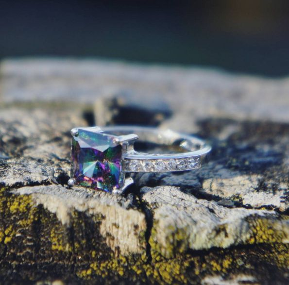 Mystic Topaz Ring: A breathtaking romantic piece which makes a perfect present. Mystic topaz set in princess design with Swarovski crystals accent on band. Real rhodium electroplated over silver.  $105.00