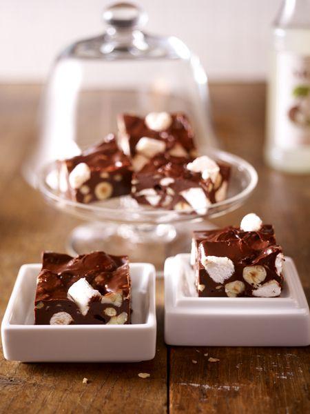 Marshmallow-Konfekt  Zutaten (15 Stücke)  100 g Marshmallows, 150 g Macadamianusskerne, 400 g Zartbitterkuvertüre, 1 Packung schnittfeste Nuss-Nougatmasse, 125 g Butter, Frischhaltefolie