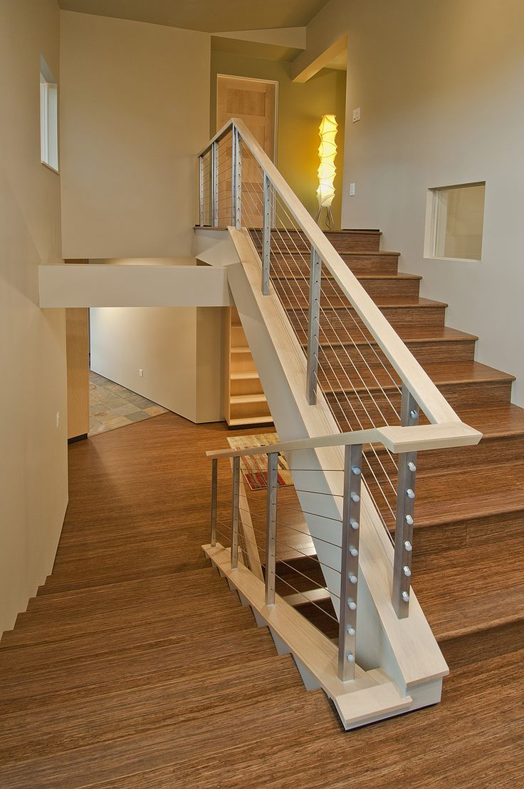 Tension wire stair railing with a funky modern floor lamp to brighten the path.