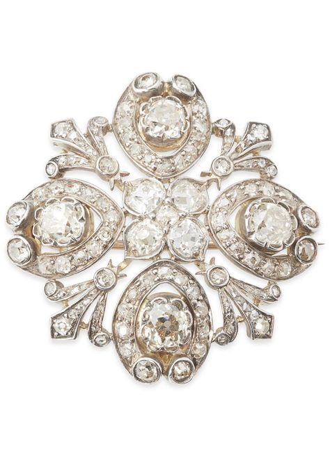 A diamond set cluster brooch. The central cluster of five old cushion cut diamonds, in a surround of diamond set fleur-de-lys and palmette clusters, each set with a large cushion cut diamond in silver, yellow metal back. Width: 40mm, estimated total principal cushion cut diamond weight: 2.00cts