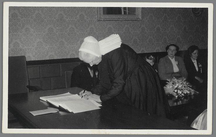 Vrouw in streekdracht ondertekent een huwelijksakte. opname gemaakt tijdens een huwelijksplechtigheid in februari 1957 te Rijssen. De vrouw is in de rouw, gezien haar effen muts, welke normaliter van motieven is voorzien. #Overijssel #Salland #Saksen #Rijssen