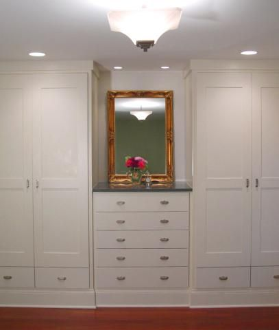 Matching built-in closets with varying height rods eliminated the need for a walk-in closet while allowing all but out-of-season clothing to be easily accessible. Drawers under the doors hold shoes.