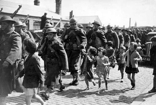 Marching through the streets of Belfast,Northern Ireland, a novelty for the local children,some of the first American troops to pass through Northern Ireland.34TH Div. Jan 1942. A discreet presence by both military personnel & civilian building contractors, preparing army, navy & air force bases, & a few aviators for experience with RAF Coastal Command, had been working behind the scenes since at least 1941. The accent? They were Canadians of course!