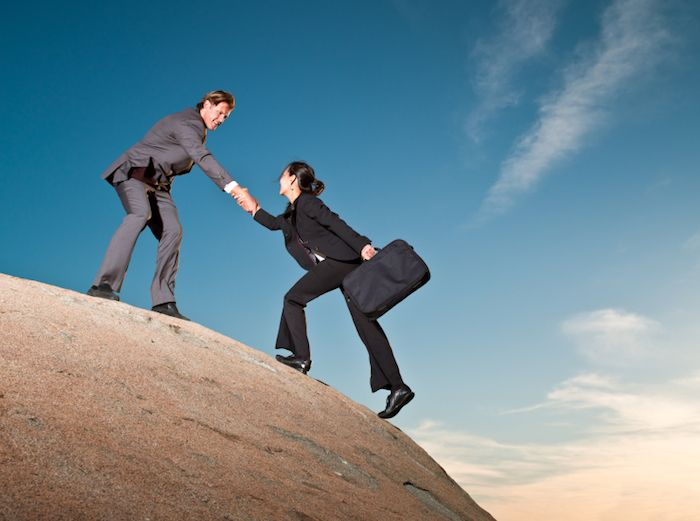 Two business people helping each other up a cliff.   Jaalsazi ...