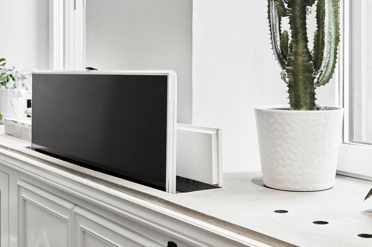 hidden tvs - Flat screen on a pop up lift concealed in a living room cabinet of a Swedish pre World War II apartment - jurnaldedesigninterior.com via Atticmag