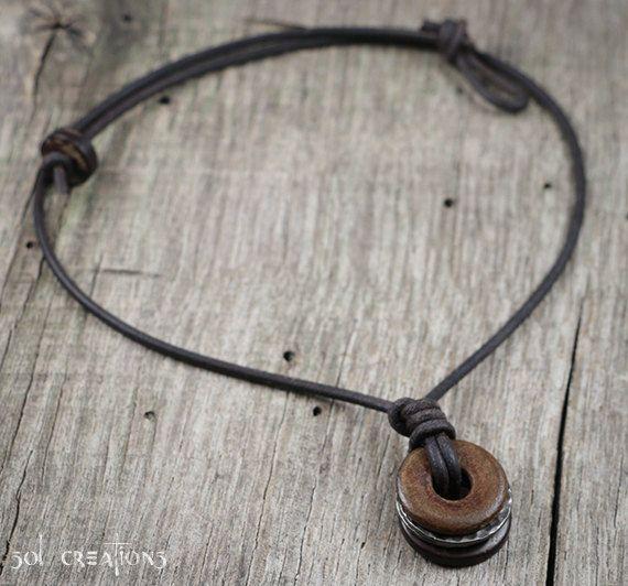 Collier en cuir pour hommes, fait à la main avec cordon en cuir marron foncé de 2mm et un pendentif réalisé avec un anneau en bois coco, bague en corne naturelle et deux bagues en étain martelé. Doit être robuste, indémodable et durable... comme collier d'un homme.  Taille du pendentif: 20mm (0,8 pouce). J'utilise seulement la plus haute qualité cordon en cuir disponible sur le marché. Il obtient sa couleur à travers un processus de teinture naturelle, ce qui lui permet de maintenir son…