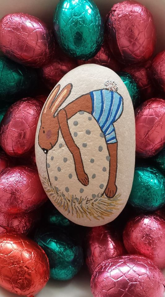 Bunny laying on egg painted rock