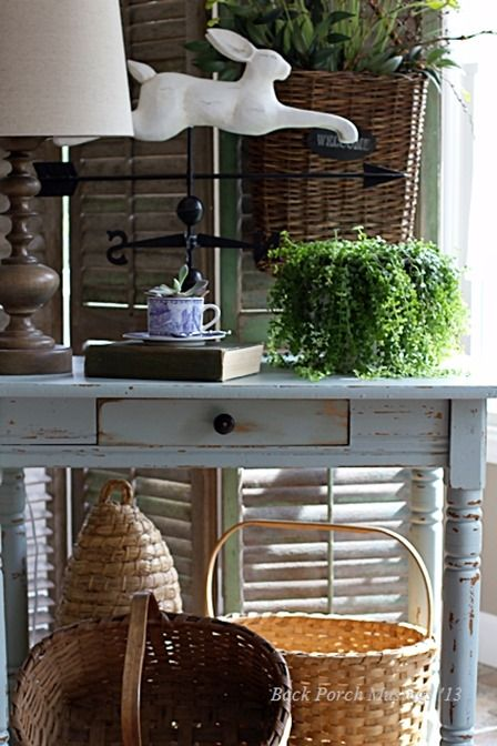 Pretty vignette with rabbit weather vane, pretty blue table, and lots of baskets